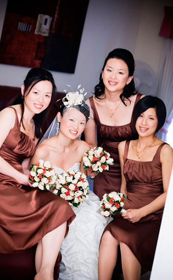 Asian bride with her bridesmaid holding bouquets