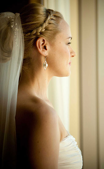 Bride with a braided wedding hairstyle and veil looking at the window