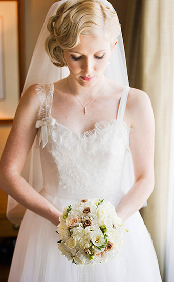 Bride with a fingerwave inspired hair looking down and holding a bouquet