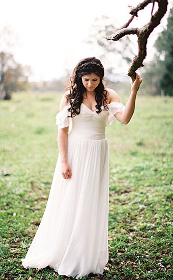 Full body shot of a curly hair bride outdoors