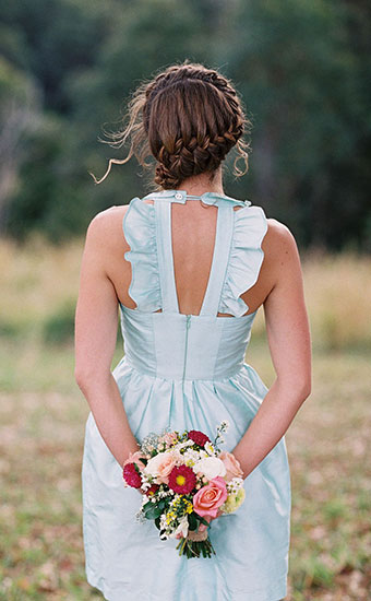 Back view of a bridesmaid in lightblue dress with a braid hairstyle holding a bouquet