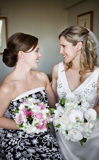 Bride and Bridesmaid smiling at each other while holding bouquet