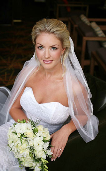 Blonde bride with a white rose bouquet smiling