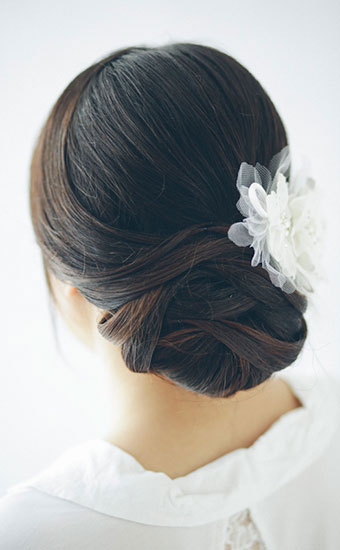 Weaved wedding hairstyles with a white cloth rose