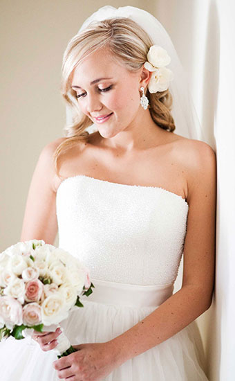 Bride with a blonde curly hairdos and white rose and veil
